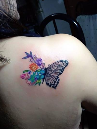 Mariposa y flores tatuaje realizado por Ginebra Lilith