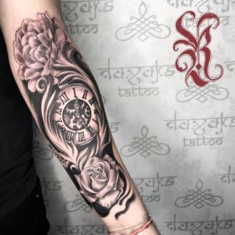 Reloj y flores tatuaje realizado por Rolando Castillejos