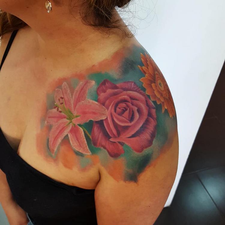 Flores en el hombro tatuaje realizado por Carlos Koyote Ramirez