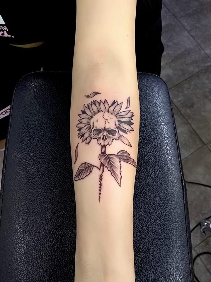 Flor con cráneo tatuaje realizado por Adan dados uno
