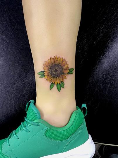 Girasol en espinilla tatuaje realizado por Adan dados uno