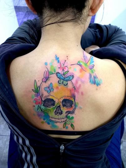 Cráneo y colibrí en acuarela tatuaje realizado por Adan dados uno