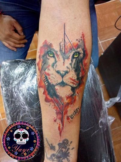 León en brazo tatuaje realizado por Yayi Yelitza