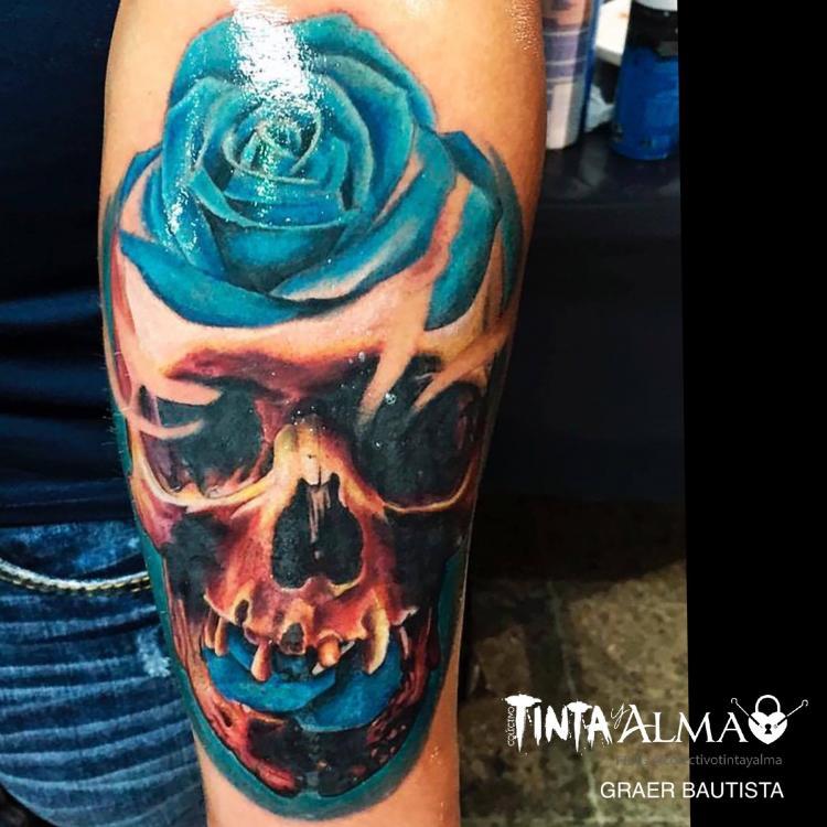 Cráneo y rosa azul tatuaje realizado por Tinta y Alma