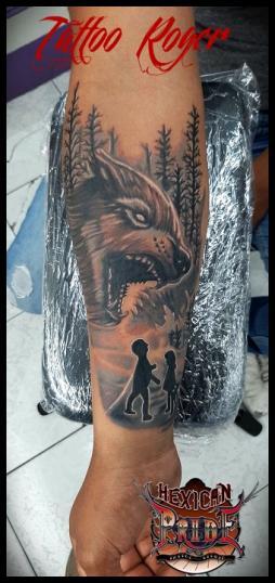 Lobo con siluetas de niños y bosque tatuaje realizado por Roberto Girón