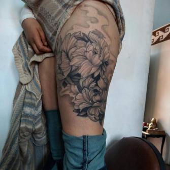 Poenias en la pierna tatuaje realizado por Carlos Koyote Ramirez