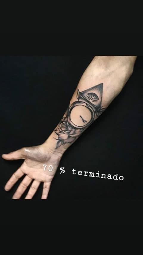 Reloj con rosa y triangulo iluminaty a un 70% de terminar  tatuaje realizado por Doble V Tattoos