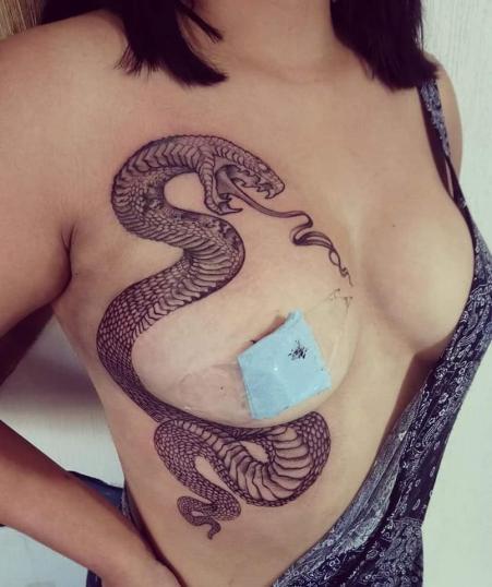 Serpiente en las costillas y pecho tatuaje realizado por Ruth Winchester