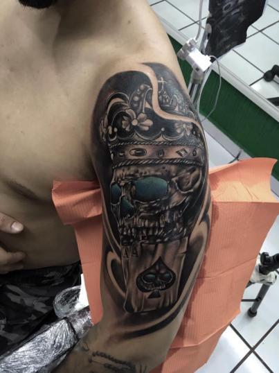 Cráneo con corona tatuaje realizado por Raphael Rios