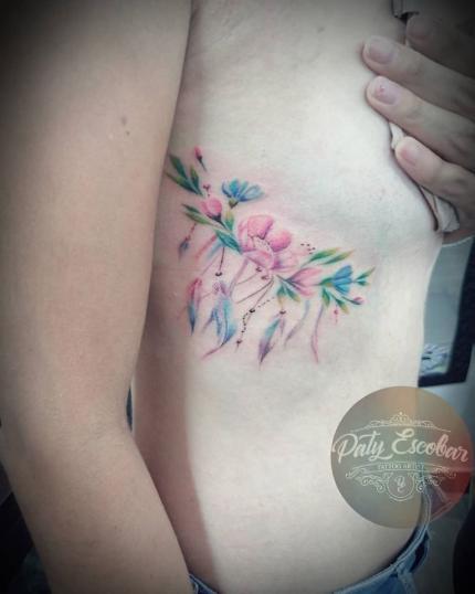 Flores colores debajo del pecho tatuaje realizado por Paty Escobar