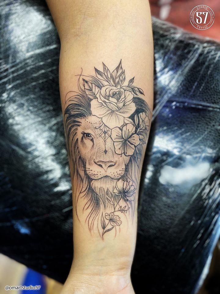 León y flores  tatuaje realizado por Omar Mendoza
