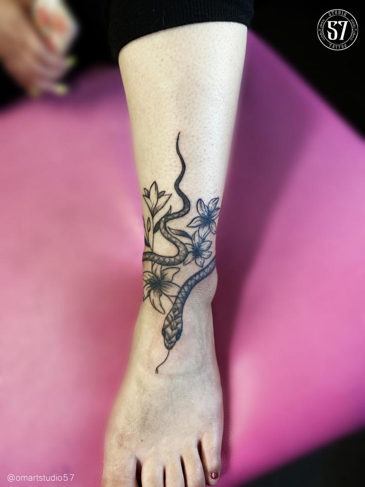 serpiente y cataleyas  tatuaje realizado por Omar Mendoza