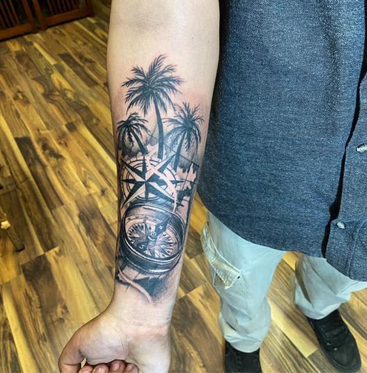 brujula y palmeras  tatuaje realizado por Omar Mendoza